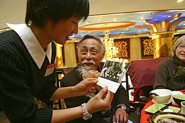 Uebersetzer Zhou Chun, translator Prof. Zhou Chun, shows a waitress a photo of him with Chou En Lai