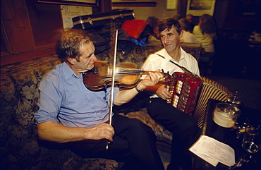 Two men playing traditional music on violin and accordion in Gus O'Connor's Pub, Doolin, County Clare, Ireland00058539