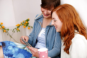 Two young women looking at photographs