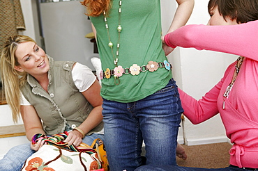 Young woman trying on new belt in clothes shop