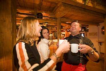 Two girls and a man enjoying an Apres-ski party at Purzelbaum Alm, Flachau, Salzburger Land, Austria
