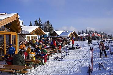 Skiers sitting in front of the Birkhahnalm and Griessenkarhaus, Flachau, Salzburger Land, Austria