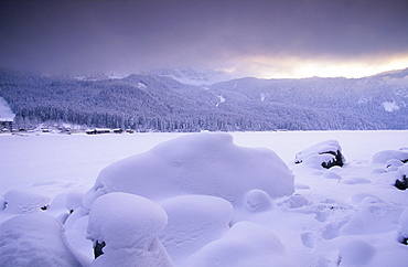 Europe, Germany, Bavaria, near Grainau, snow coverd stones on the frozen up Eibsee with Bavarian Alps