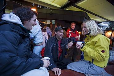 Group of young people enjoying an Apres Ski party on terrace of Papperla Pub, Zermatt, Valais, Switzerland