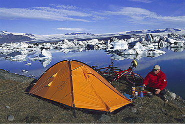 Mountainbiker cooking near his tent, Camping, Jokulsarlon, Glacier lake, Iceland00015130