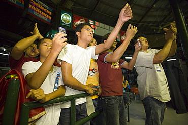 Spectators applauding during a Thai boxing competition, Lumphini Stadium, Bangkok, Thailand