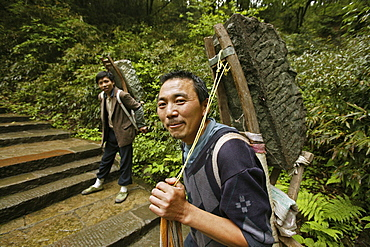 Two porters carrying heavy load on the pilgrimage route, Emei Shan, Sichuan province, China, Asia
