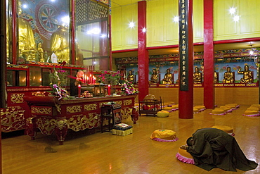 Praying monk at main hall of the Wannian monastery, Emei Shan, Sichuan province, China, Asia