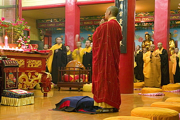 Praying monks at the main hall of the Wannian monastery, Emei Shan, Sichuan province, China, Asia