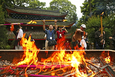 Pilgrims burning incense sticks in front of temple, Wannian monastery, Emei Shan, Sichuan province, China, Asia