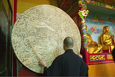 Monk standing in front of a gong, Wannian monastery, Emei Shan, Sichuan province, China, Asia