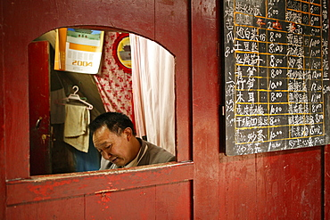 Man sitting in a booth next to the menu, canteen of the Xixiang Chi monastery, Emei Shan, Sichuan province, China, Asia