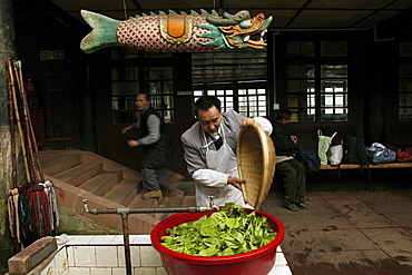 Man washing vegetables, Canteen of the Xixiang Chi monastery, Emei Shan, Sichuan province, China, Asia