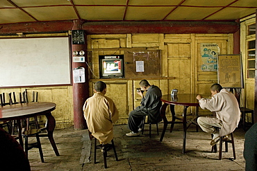 Monks eating at the canteen in front of the television, Xixiang Chi monastery, Emei Shan, Sichuan province, China, Asia