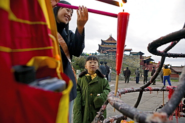 Woman and child lighting a candle in the morning, Emei Shan mountains, Sichuan province, China, Asia