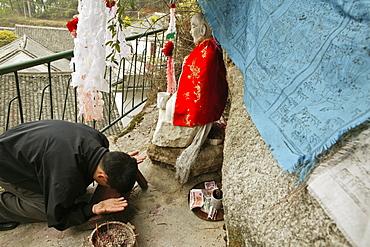 pilgrim prays in front of small statue of monk Shenizi, Nantai temple, Heng Shan south, Hunan province, Hengshan, Mount Heng, China, Asia