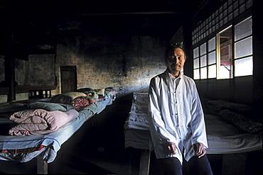 A monk standing at pilgrim's dormitory at Qunxian monastery, Hua Shan, Shaanxi province, China, Asia