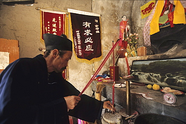 Taoist hermit monk prays at his altar, cliff hermiatge, Hua Shan, Shaanxi province, Taoist mountain, China, Asia