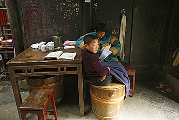 Two boys doing homework in a residential house at the village Hongcun, Huangshan, China, Asia