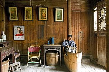 Man with cat sitting at a foot warmer Huo Tong, Hongcun, Huang Shan, China, Asia
