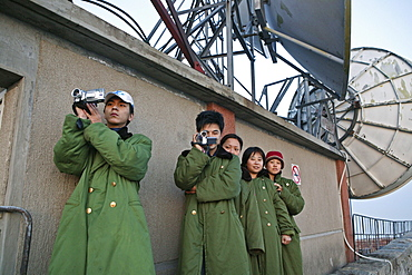 Tourists at the summit of Mount Tai filming the sunset, military coats can be rented out, Tai Shan, Shandong province, World Heritage, UNESCO, China