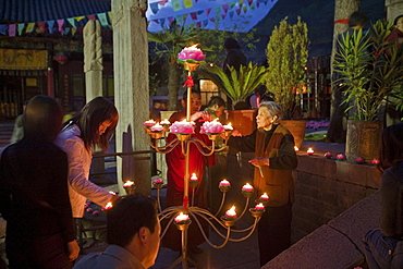 Lighting the candles during the birthday celebrations for Wenshu, Shuxiang temple, Mount Wutai, Wutai Shan, Five Terrace Mountain, Buddhist Centre, town of Taihuai, Shanxi province, China
