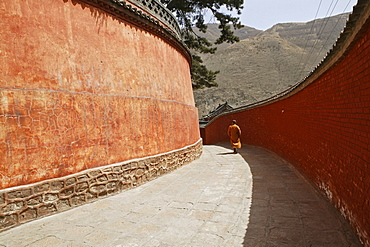 Monk walking to Pusa Ding Summit, high walls of the monastery, Xiantong Monastery, Wutai Shan, Five Terrace Mountain, Buddhist Centre, town of Taihuai, Shanxi province, China