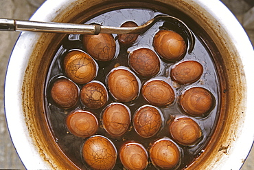 Tea eggs, hard boiled eggs in black tea, soy sauce and spices, typical snack, chopsticks, China