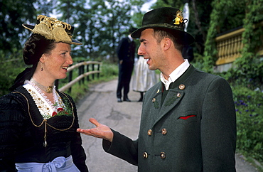 Young couple in dirndl dress and traditional dress talking to each other, pilgrimage to Raiten, Schleching, Chiemgau, Upper Bavaria, Bavaria, Germany
