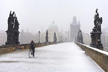 Man on a bicycle riding over Charles Bridge, Prague, Czech Republic