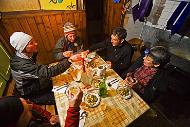 A group of people in a moutain hut toasts with a glass of Raki brandy, Demjanica cabin, Pirin Mountains, Bulgaria, Europe