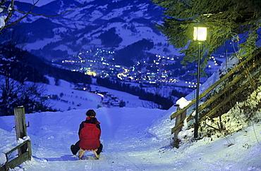 Sledging on illuminated toboggan-run at night, Alpendorf, St. Johann im Pongau, Salzburg, Austria