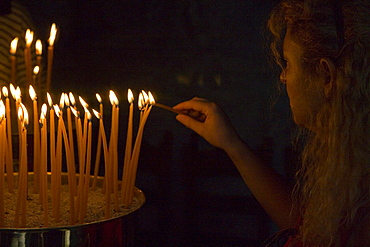 Person lighting candles in a cave of the monastery of the Apocalypse, Patmos, Dodecanese Islands, Greece