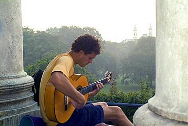Young man playing guitar, Monopteros, English Garden, Munich, Bavaria, Germany