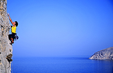Kalymnos, Greece a woman climbs on a vertical rock pillar above the Aegean Sea, Europe, MR