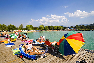 Young people sunbathing on landing stage at Strandbad Klagenfurt, Lake Woerthersee (biggest lake of Carinthia), Klagenfurt, Carinthia, Austria