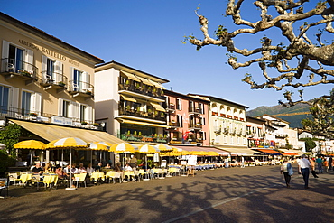 People passing pavement cafe of the Restaurant and Hotel Moevenpick Albergo Carcani at harbour promenade, Ascona, Lake Maggiore, Ticino, Switzerland