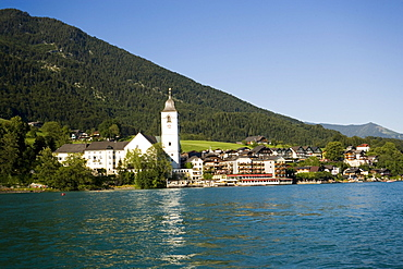 View over lake Wolfgangsee to parish and pilgrimage church and Hotel Im Weissen Roessel am Wolfgangsee, St. Wolfgang, Upper Austria, Salzkammergut, Austria