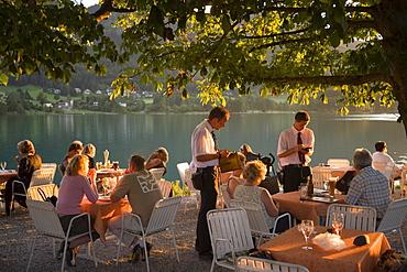 Waiters taking order for guests in the open air area of a restaurant, Lake Fuschl, Fuschl am See, Salzkammergut, Salzburg, Austria