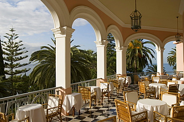 Chairs and tables on the sunlit terrace of Reids Hotel, Funchal, Madeira, Portugal