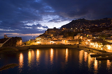 Illuminated houses at harbour in the evening, Camera de Lobos, Madeira, Portugal
