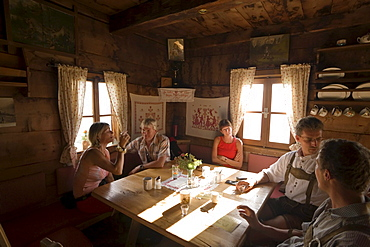 Group of people sitting in the Karseggalm Hut (1603 m, one of the oldest mountain hut in the valley), Grossarl Valley, Salzburg, Austria