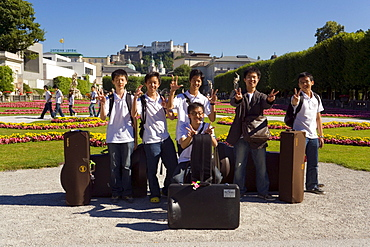Members of the Asian Youth Orchestra smiling at camera, Mirabell castle and garden, Hohensalzburg Fortress, largest, fully-preserved fortress in central Europe, in background, Salzburg, Salzburg, Austria
