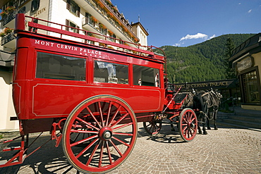 Red carriage of the Mont Cervin Palace parking in front of the Hotel, Zermatt village, Zermatt, Valais, Switzerland
