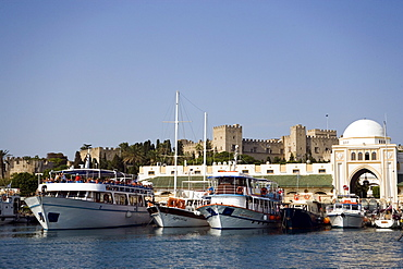 Ships and boats anchoring in Mandraki harbour (translated literally: fold), Palace of the Grand Master and Nea Agora in background, Rhodes Town, Rhodes, Greece