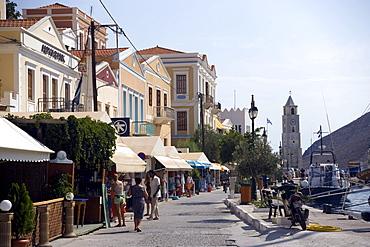 View along promenade to clocktower, Gialos harbour, Simi, Symi Island, Greece