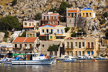 Fishing boats and rowboats anchoring in harbour Gialos, picturesque houses in background, Simi, Symi Island, Greece