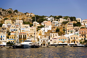 Yacht and sailing boats anchoring at quay of harbor Gialos, Simi, Symi Island, Greece