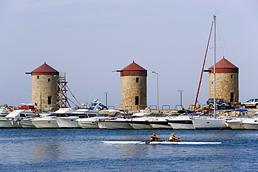 Women rowing in the Mandraki harbour (translated literally: fold), anchoring ships and windmills on mole in background, Rhodes Town, Rhodes, Greece