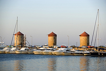 View over Mandraki harbour (translated literally: fold) with anchoring ships to windmills on mole, Rhodes Town, Rhodes, Greece